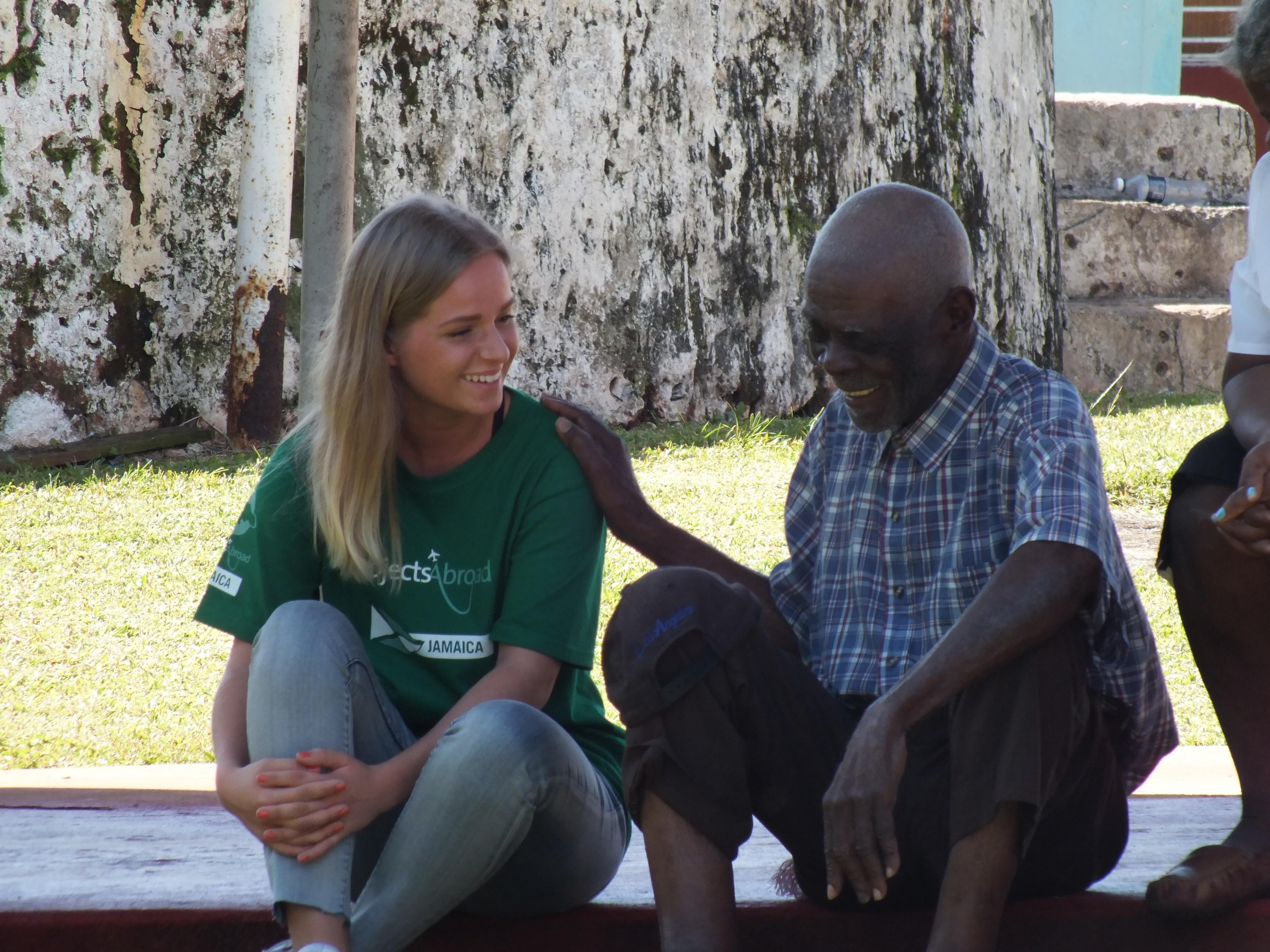 Projects Abroad Care volunteer speaks to a local man within the Community Outreach Day during Psychology placements in Jamaica.